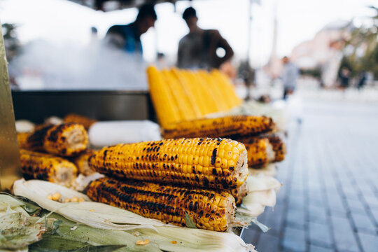 Raw and grilled corn cobs on stall