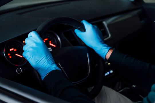 Man with protective gloves inside a car