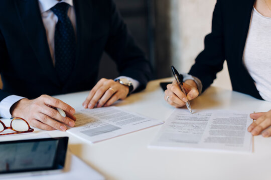 Anonymous business partners signing contract during meeting