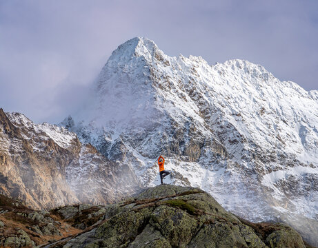 Women in yoga tree pose in front of snow covered mountain