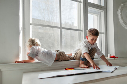 Little boys drawing in the white room.