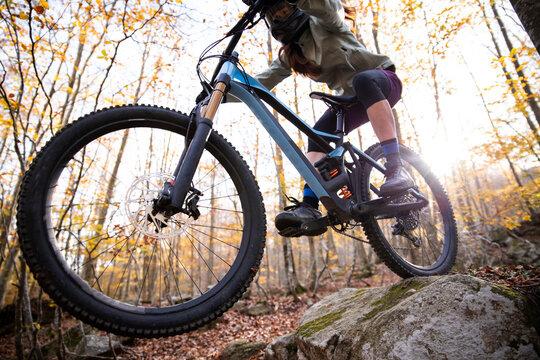 Woman in helmet riding mountain bike in forest