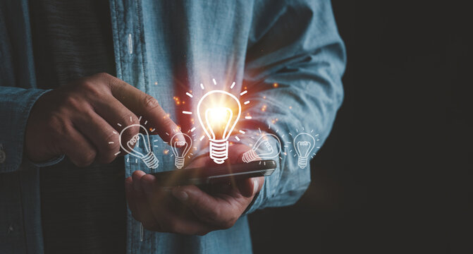 Businessman touching smartphone with light bulbs on the phone screen. ideas of new ideas with innovative technology and creativity.