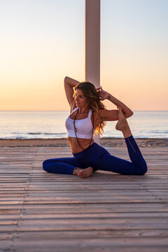 Flexible woman doing yoga in Mermaid pose on beach