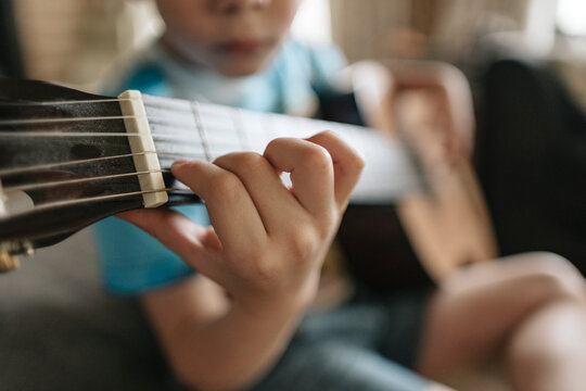 A young boy is learning to play the guitar.