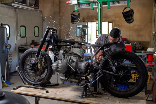 Focused mechanic working with motorcycle in garage