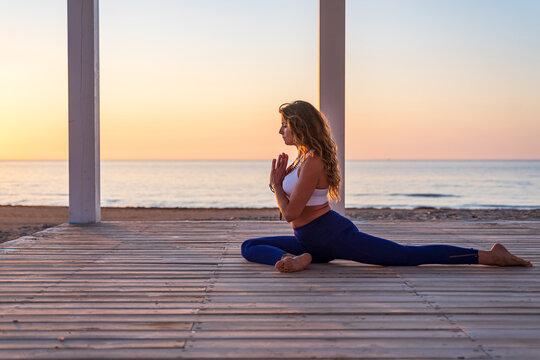 Woman practicing yoga in Pigeon pose on seashore