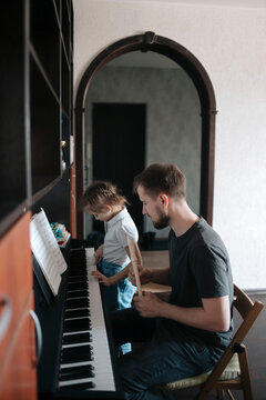 Dad and daughter play music at home.