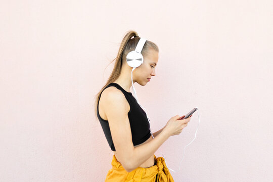 Young woman listening to music on the phone isolated on bright background