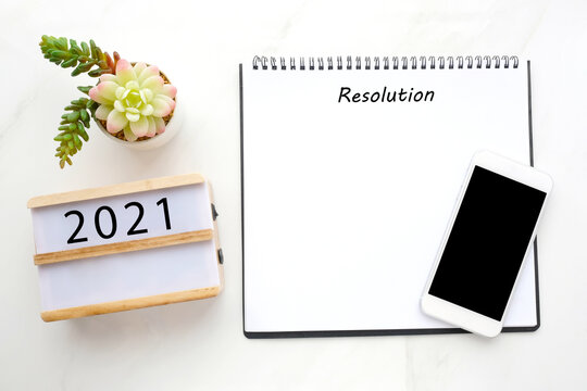 2021 resolution on blank notebook paper, smart phone with blank screen on white marble background, 2021 new year mock up, template, flat lay