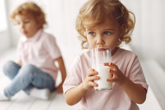 Children in a studio. Little girl with her brother. Boy in a pink t-shirt. Kids drinking a milk.