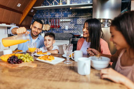 Latin family eating healthy breakfast in the kitchen