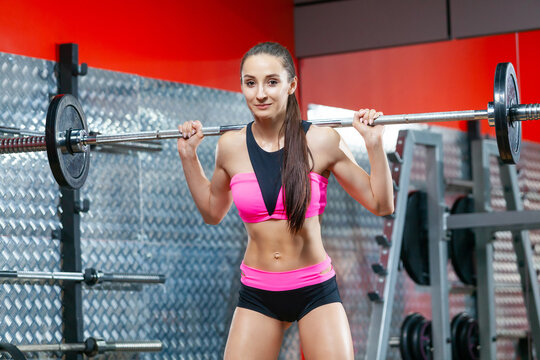 Photo of a happy muscular woman holding a barbell on her shoulders ready to do exercises in gym
