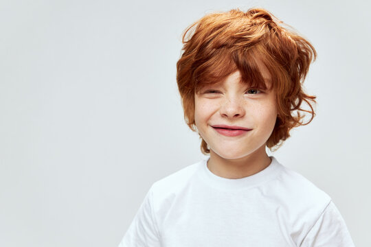Sly red-haired boy with narrowed eyes conceived something bad white t-shirt cropped view