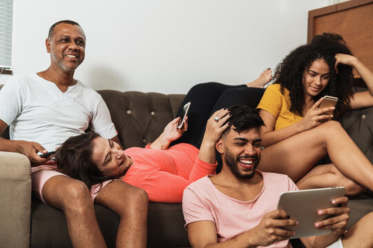Latin American family sitting on the couch, using technology. Father watching TV, curly-haired daughter and mother using cellphone and son fiddling with digital tablet