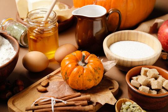 Ingredients for preparing pumpkin pie on color background