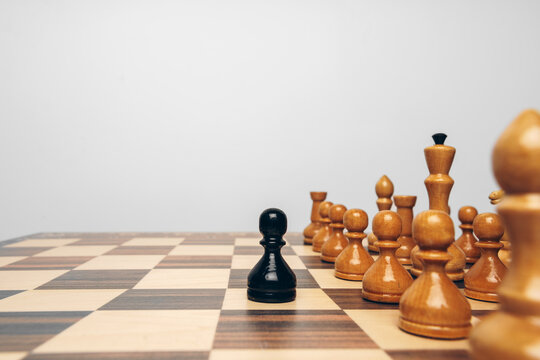 Chessboard with wooden figures against grey background