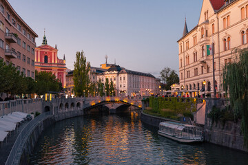 The promenade on the Ljubljanica river in the slovenian capital city Ljubljana with the Triple...