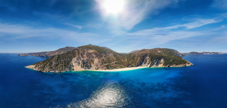 Wide aerial panoramic view to the popular beach of Myrtos on the Ionian island of Kefalonia, Greece, with turquoise sea and sunshine during summer time