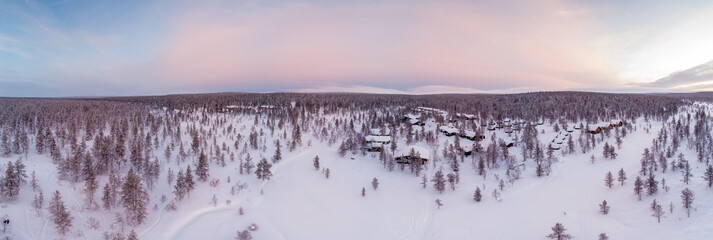 Visit Lapland Holidays. Aerial drone panorama shot of the forest covered in snow winter and the village inside the Arctic Circle. Lapland, Finland. Winter sunrise. Igloos and cabins covered with snow