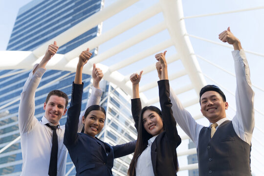 Four executives in a row, Business team standing and cheering in front of modern office, Leadership Concept