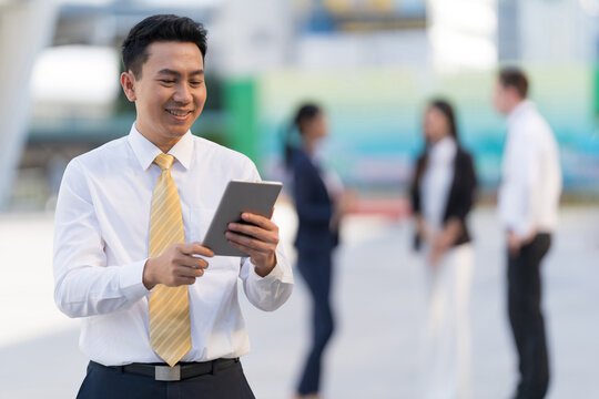 Portrait of smiling businessman looking at tablet