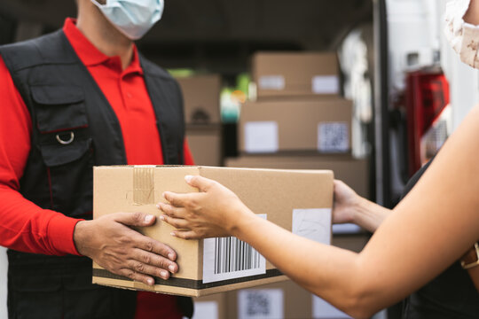 Delivery man wearing face protective mask to avoid corona virus spread - Young woman receiving an online order package from courier express
