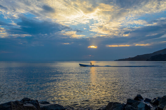 Silhouette of a lone fisherman in a fishing boat starting for work during the first light in the morning.