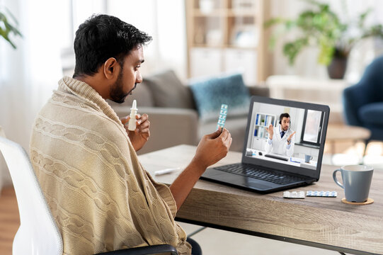 healthcare, technology and people concept - sick indian man in blanket with thermometer having video call or online consultation with doctor on laptop computer at home