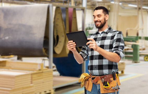 industry, technology and work concept - happy smiling worker or builder with tablet pc computer and tools over woodworking factory background