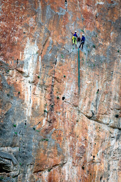 Two athletes practicing climbing on a vertical wall and high above the ground.