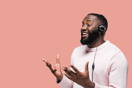 Afro-american call center worker with headphones in casual wear standing on a pink isolated background while communicating with a client and smiling