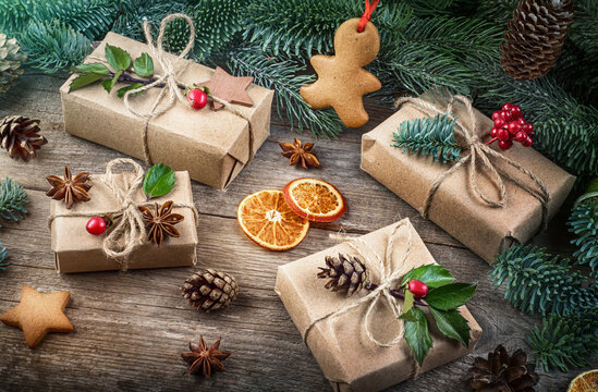 Christmas and New Year background with decorations. Christmas gift, pine cones, fir branches, gingerbreads on wooden background.