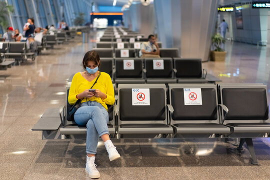 A beautiful woman is waiting for her flight, sitting in the airport lounge in a protective mask with a phone in her hands.