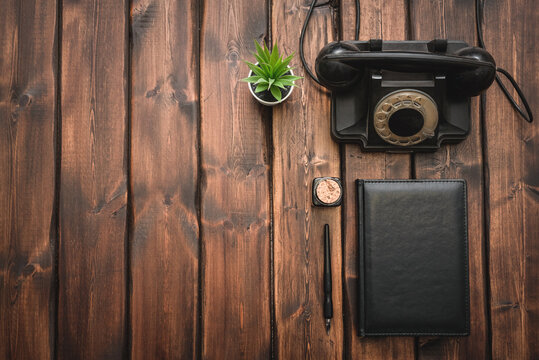 Black leather book and rotary phone on the old wooden desk background with copy space.