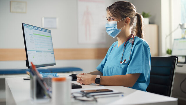 Latin American Doctor's Office: Experienced Head Nurse Wearing Face Mask Sitting at Her Desk Waiting for New Patient. Health Care Specialist Giving Advice. Patient not in Frame.