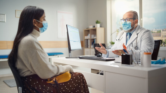 Medical Doctor Office: Latin Female Patient Talks to Friendly Experienced Physician. Medical Health Care Professional Giving Advice on Test Results, Prescribing Medicine. Both Wearing Face Masks