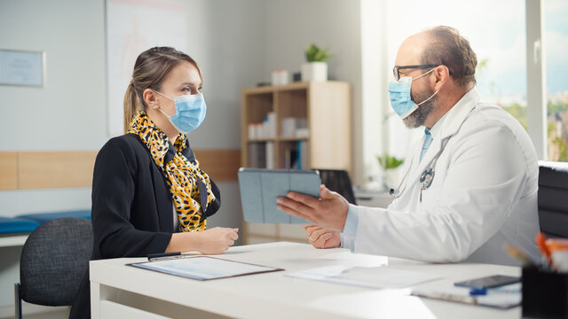 Hispanic Doctor Consultation Office: Patient Listens to Physician who Uses Digital Tablet Computer to Show, Explain Analysis Results, Prescribe Medicine, Plan Treatment. Both Wearing Face Masks