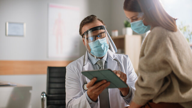 Doctor Consultation Office: Professional Physician Talks to the Female Patient, Uses Digital Tablet Computer to Explain Test Results, Treatment Plan, Prescribes Medicine. Wearing Face Masks and Visor.
