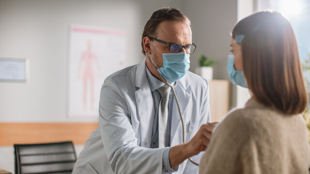 Doctor's Consultation Office: Physician Uses Stethoscope to Listen to Heartbeat and Lungs of the Female Patient. Medical Health Care Professionals Diagnosing, Treating Patient. Both Wearing Face Masks