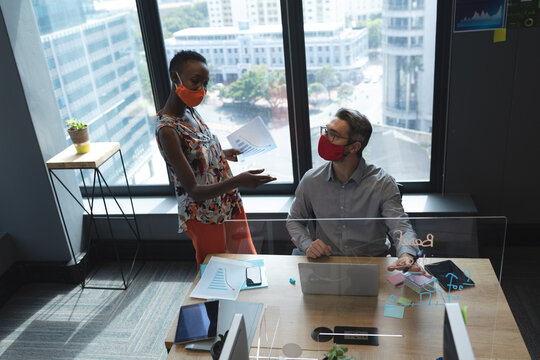 Diverse male and female colleagues wearing face masks talking to each other at modern office
