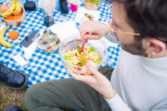 Young man outdoors having pic nic eating a healthy and vegetarian bowl of greens and salad