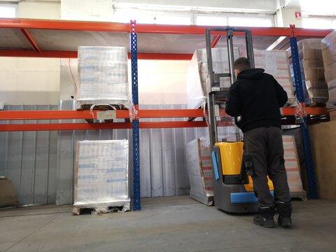 Magasinier transportant des palettes à l'entrepôt