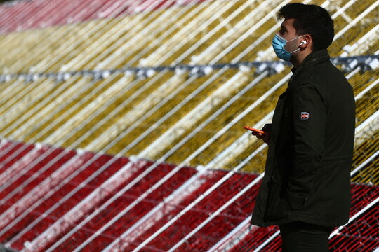 A man wearing a single-use protective mask stands beside a Christmas decoration in the colours of the Spanish flag in Madrid