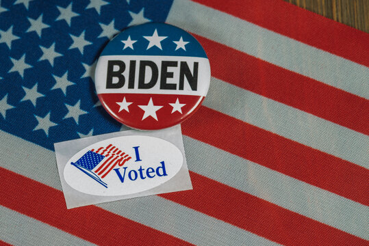 Washington DC--July 5, 2020; Round red white and blue Joe Biden campaign button next to oval shaped  I Voted sticker on American flag and wooden table top
