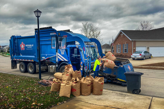 Shiloh, IL—Nov 10, 2020; Republic Services waste hauler truck and driver picking up compostable yard waste in lawn and leaf bags in residential area