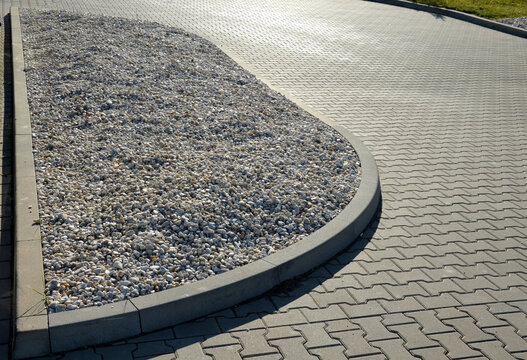 flower bed by the parking lot mulched with pebbles. it is light non-flammable and is not carried away by the wind like bark. a strip of river pebbles on a flowerbed with boulders and grasses pavement
