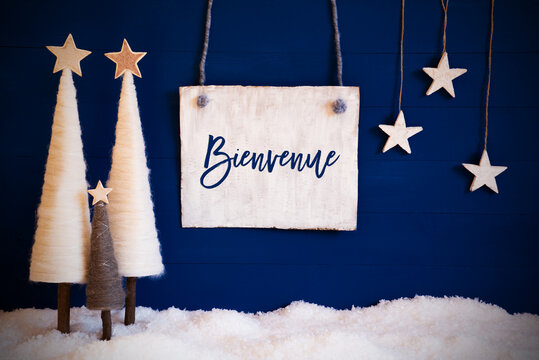 Christmas Decoration Like White Tree With Star On Blue Background. White Snow On Ground. Sign With French Calligraphy Bienvenue Means Welcome