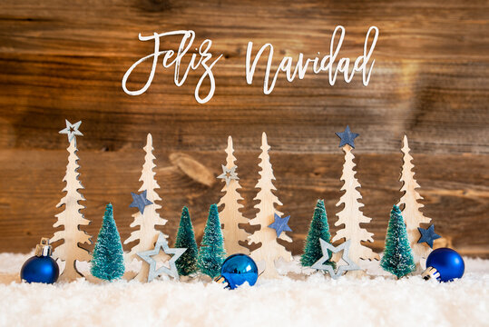 Christmas Trees With Spanish Text Feliz Navidad Means Merry Christmas. Christmas Decoration Like Blue Star Ornament And Balls. Brown Rustic Background With Snow.