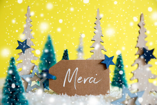Label With French Text Merci Means Thank You. Christmas Trees With Star Decoration And Ornament. Yellow Background With Snow And Snowflakes